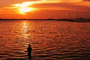 silhouette image of a fisherman in the water with golden reflection of a sunset.